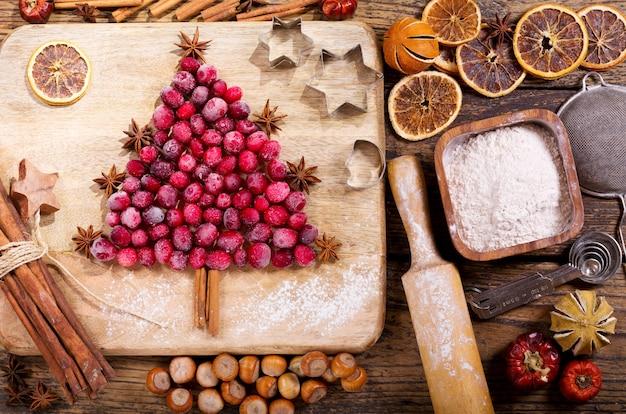 Рождественская еда. ингредиенты для приготовления рождественской выпечки: ель из замороженной клюквы, кухонная утварь и сухофрукты на деревянном столе, вид сверху