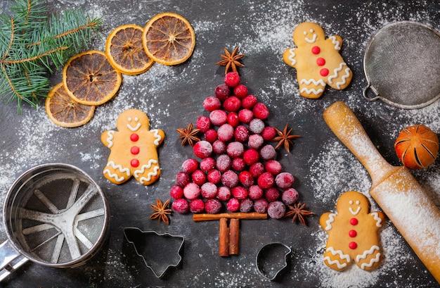 Рождественская еда. ингредиенты для приготовления рождественской выпечки: ель из замороженной клюквы, кухонная утварь и пряники на темном столе, вид сверху