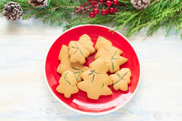 크리스마스 음식. 크리스마스 나무의 형태로 유기 크리스마스 쿠키. 지시 단계 4입니다. 나무 흰색 배경 및 주위 장식에 빨간 접시에 구운 된 쿠키. 가정식.