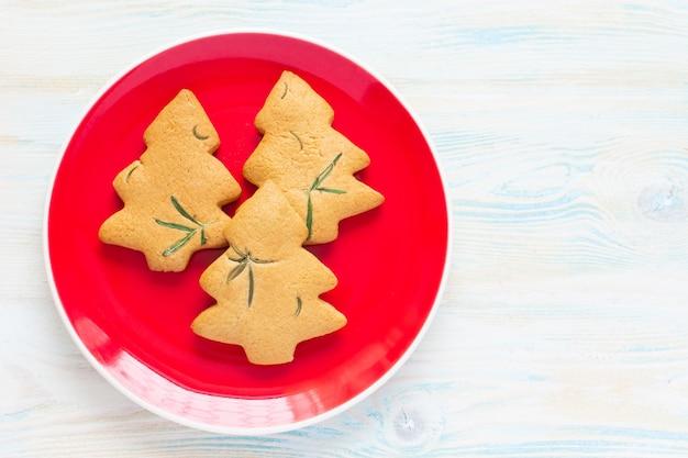 크리스마스 음식. 크리스마스 나무의 형태로 유기 크리스마스 쿠키. 지시 단계 4입니다. 나무 흰색 배경에 빨간 접시에 구운 된 쿠키. 가정식.