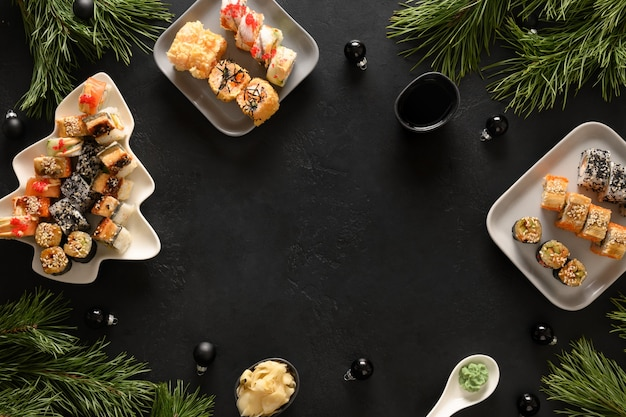Christmas food, sushi set and xmas decoration on black background. copy space. view from above. flat lay style. new year party.