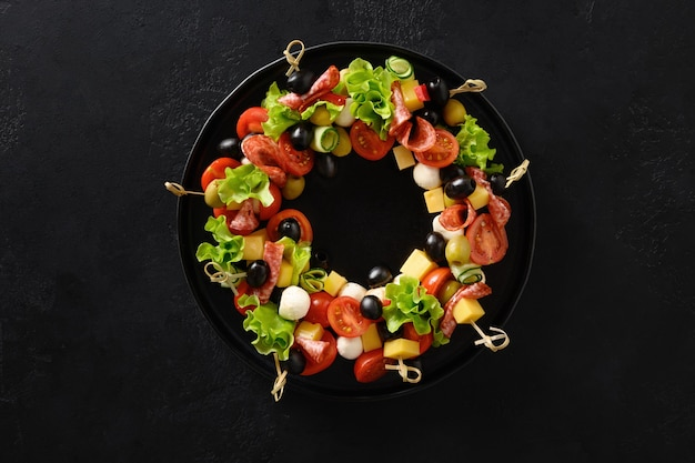 休日の軽食のクリスマスの食糧の花輪はお祝いのクリスマスパーティーのための野菜のモッツァレラチーズをカナッペ