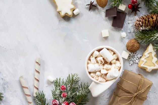 クリスマスフレームテーブルの上のホットチョコレートとジンジャーブレッドのクリスマスプレゼントのカップフラットレイ