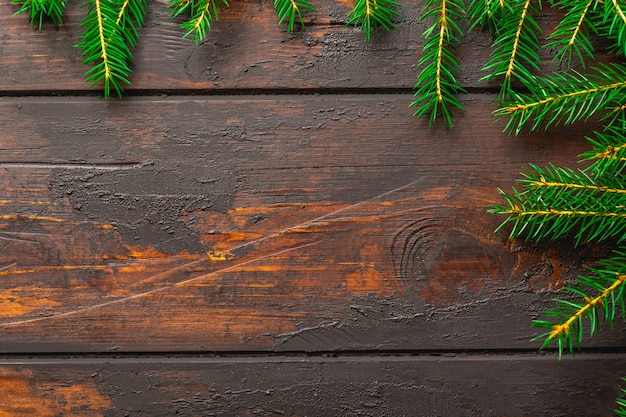 Christmas frame background. christmas fir tree branches on brown rustic wooden board with copy space.