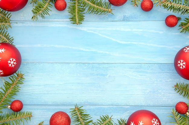 Christmas frame background with red balls decor and fir tree. on  blue background