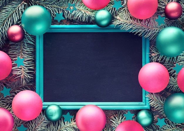 Christmas frame background on wood with blackboard, fir twigs, colorful trinkets and ribbons