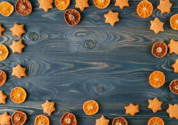 クリスマスフレーム。クリスマススパイスと木製のテーブルの乾燥オレンジスライス