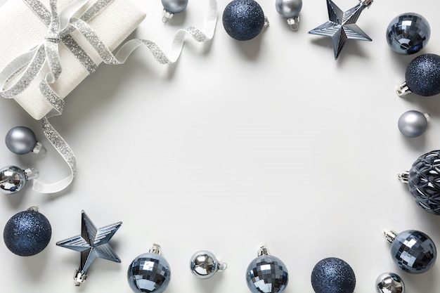 Christmas frame of classic blue balls and gift box on neutral pastel grey
