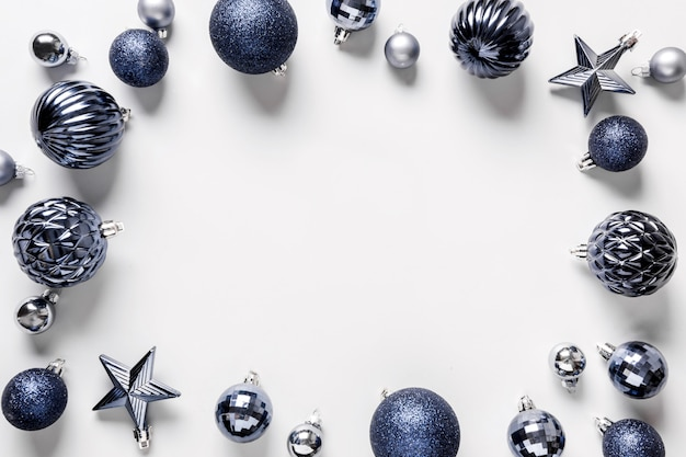 Christmas frame of classic blue balls on grey. top view. xmas border for wishes. holiday greeting card.