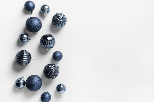 Christmas frame of classic blue balls on neutral pastel grey. top view. xmas border for wishes. holiday greeting card.