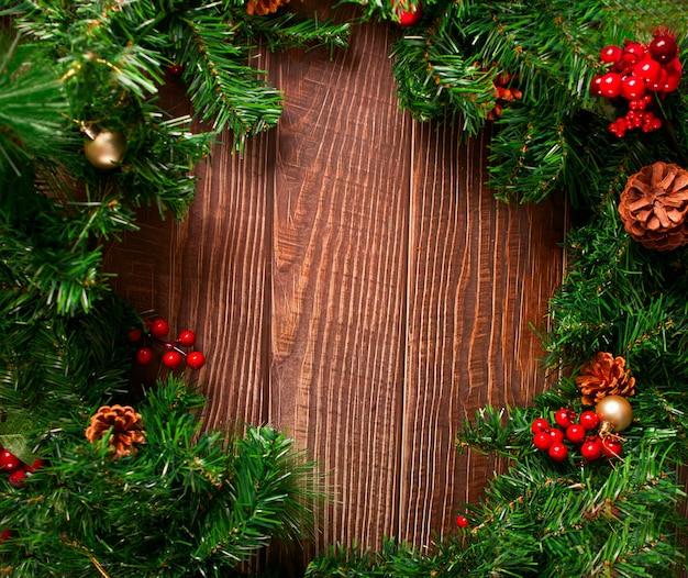 Новогоднее украшение кадра с ягодами, шишками и ветвью рождественской елки на деревянном фоне. скопируйте пространство.