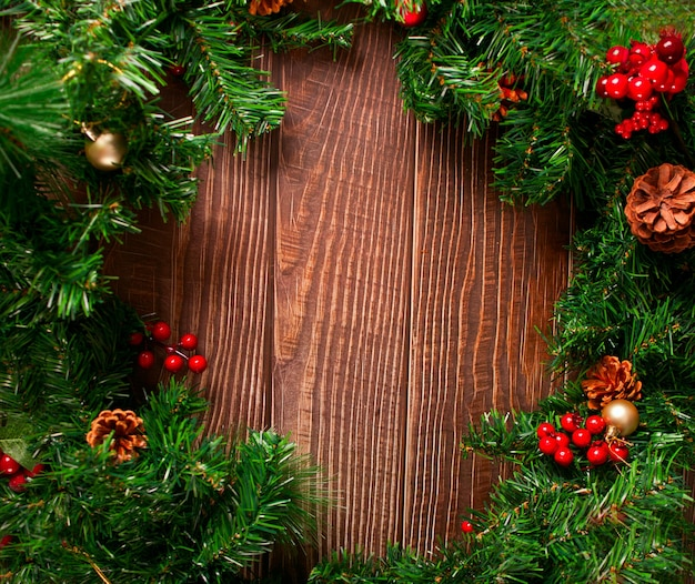 Christmas frame decoration with berries, cones and christmas tree branch on the wooden background. copy space.