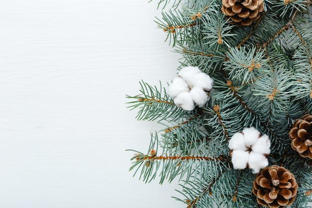 Christmas frame fir tree branches cotton bumps on white background copy space. zero waste xmas