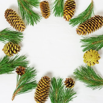 Christmas frame from branch of christmas tree, golden cones on light background with copy space.