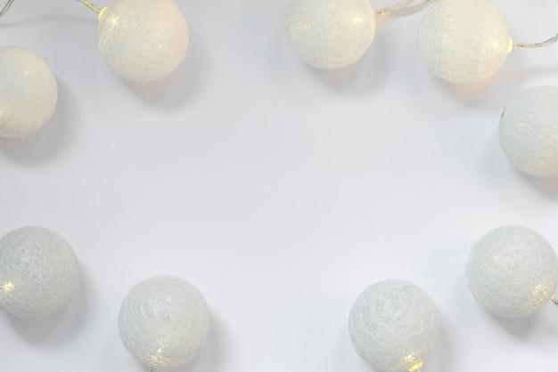 흰색에 빛나는 공 모양의 조명이 화환 장식에서 크리스마스 프레임