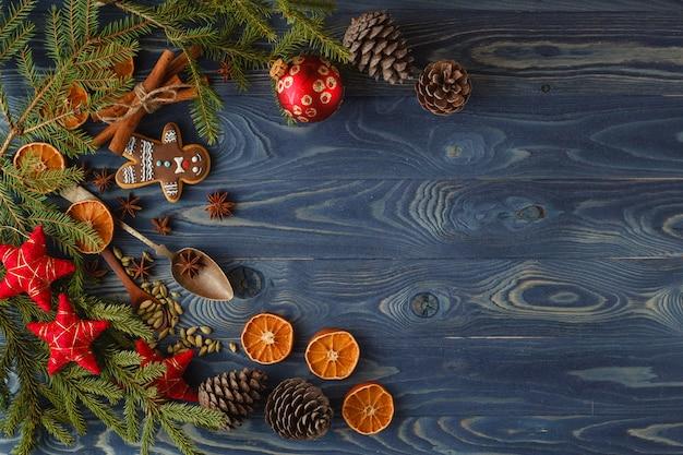 クリスマスフレーム。ジンジャーブレッドのクッキー、スパイス、木製の背景の装飾。