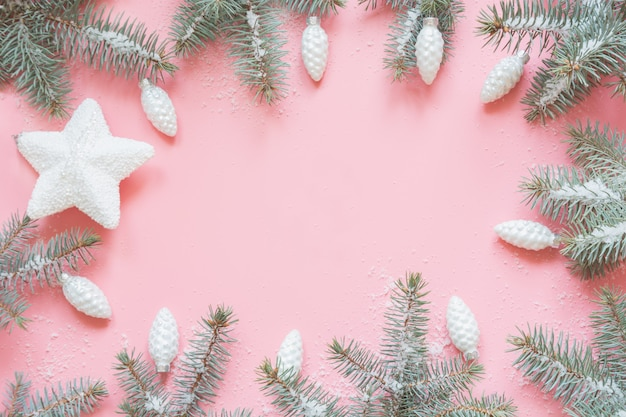 Christmas frame made of fir branches and snow on pink.xmas background. flat lay. top view with copy space