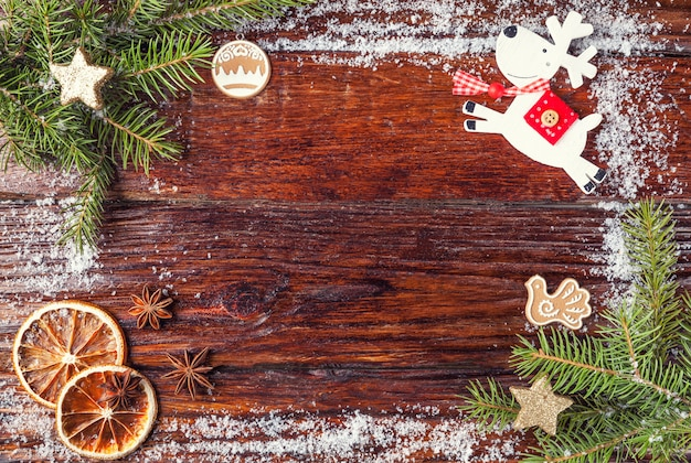 Christmas frame made of fir branches, toy deer, snow and oranges, laid out on wooden old brown background.