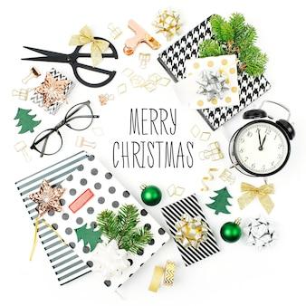 冬の装飾、目覚まし時計付きの文房具、白い背景の上の贈り物から作られたクリスマスフレーム。休日とお祝いの創造的なコンセプト。フラットレイ、上面図