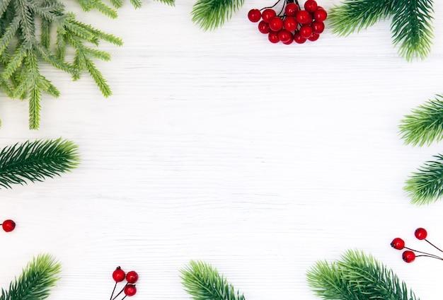 Новогодняя рамка из еловых веток, красных ягод на деревянных фоне. плоская планировка, вид сверху