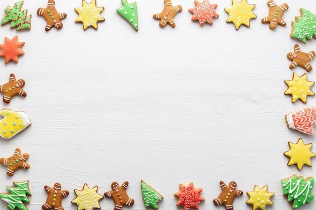 白い木製の背景にアイシングとジンジャーブレッドクッキーで作られたクリスマスフレーム