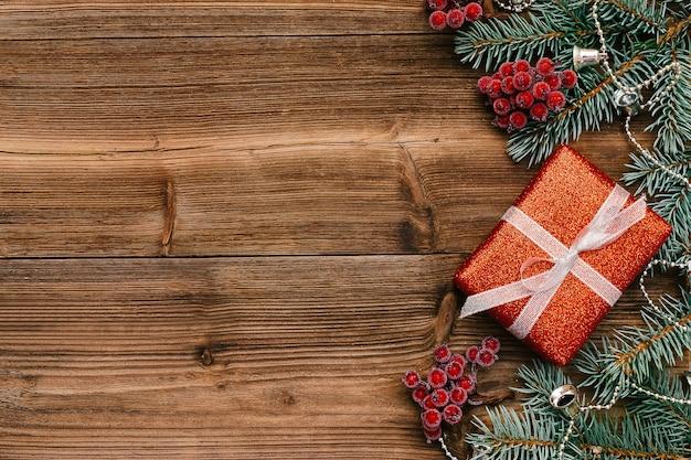 赤いギフトボックス、モミの木の枝、ガマズミ属の木の果実で作られたクリスマスフレーム。
