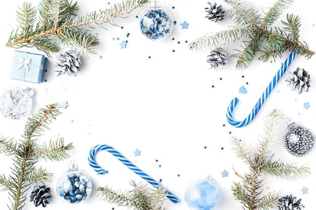 雪のモミの枝、青いキャンディケイン、装飾で作られたクリスマスフレーム。クリスマスの背景、壁紙。フラットレイ、上面図、コピースペース