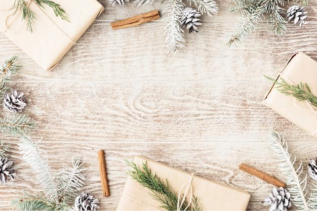 雪に覆われたモミの木の枝、松ぼっくり、茶色のクラフト紙のギフトボックスで作られたクリスマスフレーム。クリスマスの壁紙。フラットレイ、上面図、コピースペース