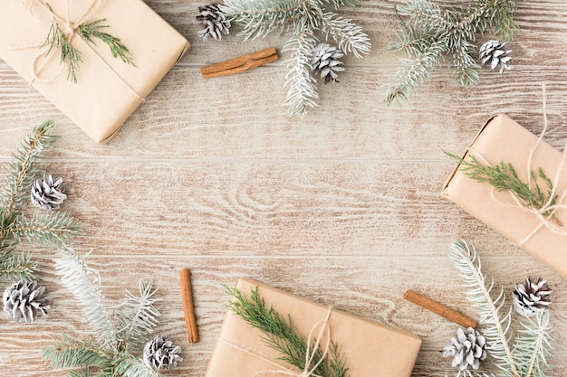 Christmas frame made of snowy fir tree branches, pine cones, gift box in brown craft paper. christmas wallpaper. flat lay, top view, copy space