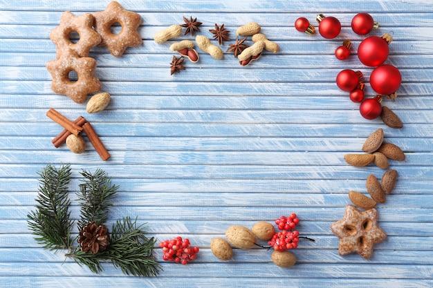 カラーの木製の背景にクッキー、ナッツ、スパイスのクリスマスフレーム