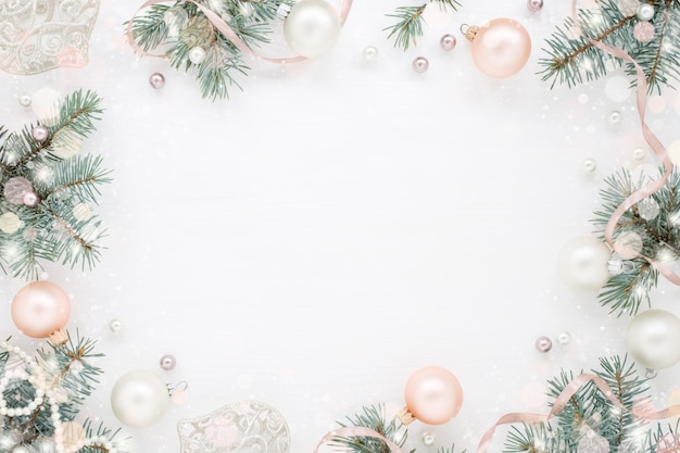 緑のモミの枝、装飾、白い表面上の真珠のクリスマスフレーム