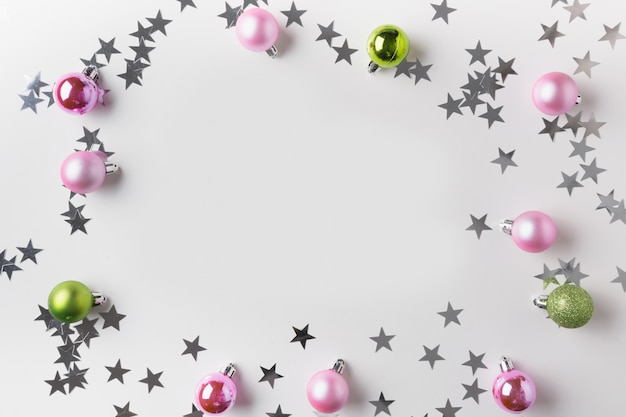 Christmas frame of silver and pink balls on white. top view. xmas background for wishes. greeting card.