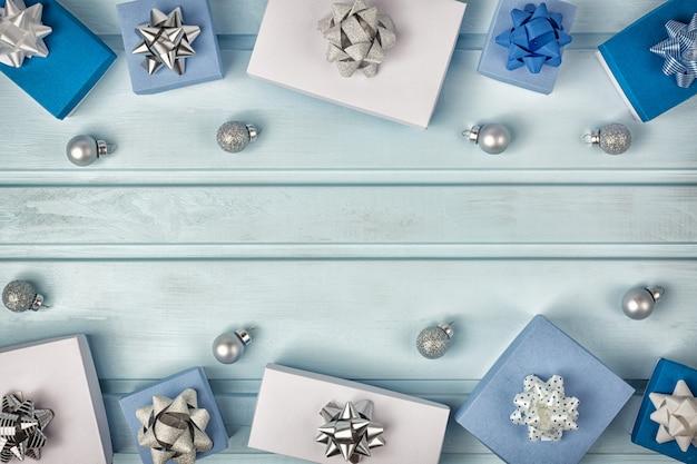 クリスマスフレーム。銀の弓で飾られた白と青のギフトボックス。小さなクリスマスボール。コピースペース。テキストのための場所と休日のレイアウト。