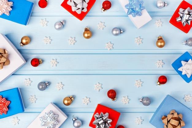クリスマスフレーム。銀の弓で飾られた白、青、赤のギフトボックス。