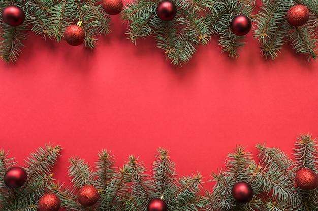 Новогодняя рамка с вечнозелеными еловыми ветками, красные шары на красном пространстве