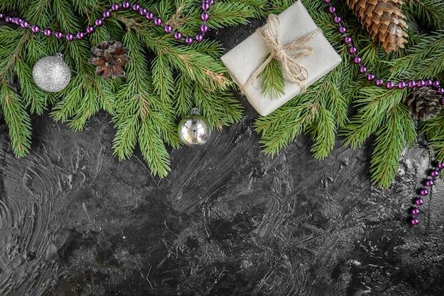モミの枝、ギフトボックス、黒い表面にマツ円錐形のクリスマスフレーム。