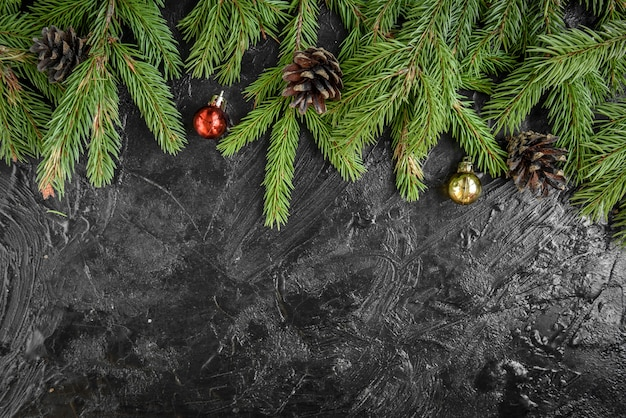 Christmas frame with fir branches, gift box and pine cones on black surface.