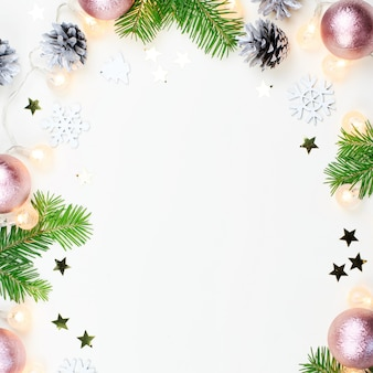 Christmas frame with fir tree branches, christmas lights, pink and beige decorations