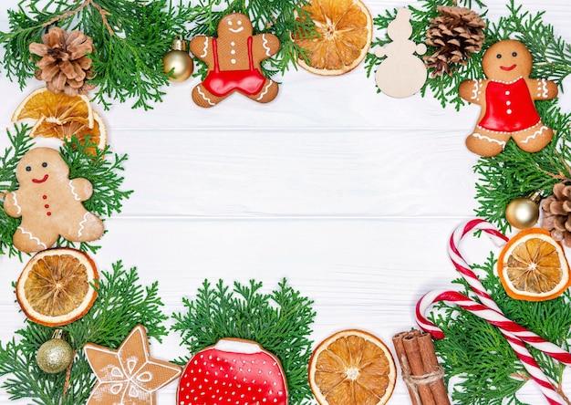 モミの木の枝、乾燥したオレンジ色のリング、クッキーのクリスマスフレーム