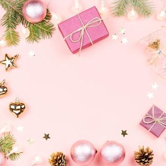 Новогодняя рамка с еловыми ветками, подарочными коробками, украшениями на розовом. копировать пространство
