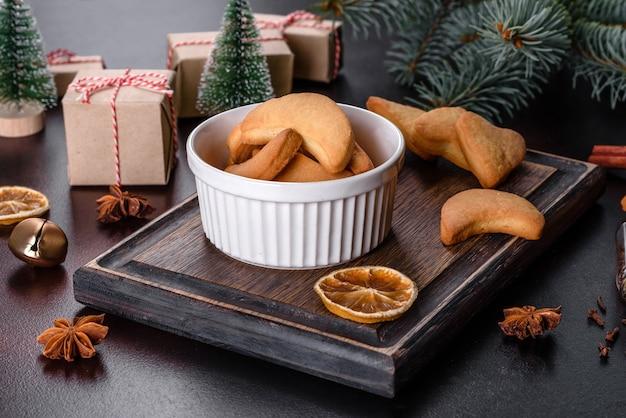 돌 배경에 전나무 나뭇가지, 진저브레드 쿠키, 향신료, 말린 오렌지 링, 크리스마스 장난감이 있는 크리스마스 프레임 프리미엄 사진
