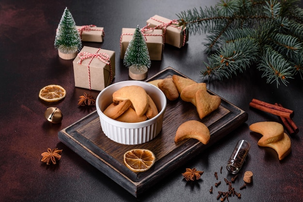 Christmas frame with fir tree branches, gingerbread cookies, spices, dried orange rings and christmas toys on stone background