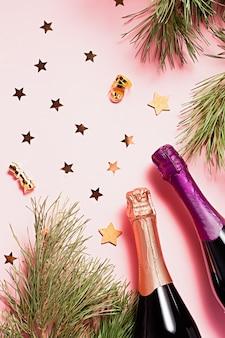 モミの木、影、シャンパンボトル、グラス、カーニバルマスク、ピンクと紫の色のクリスマスオーナメントとクリスマスフレーム。コピースペース