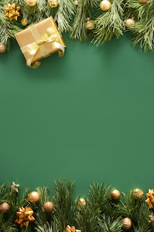 Christmas frame with golden gift and balls on green. xmas vertical banner. new 2021 year greeting card.