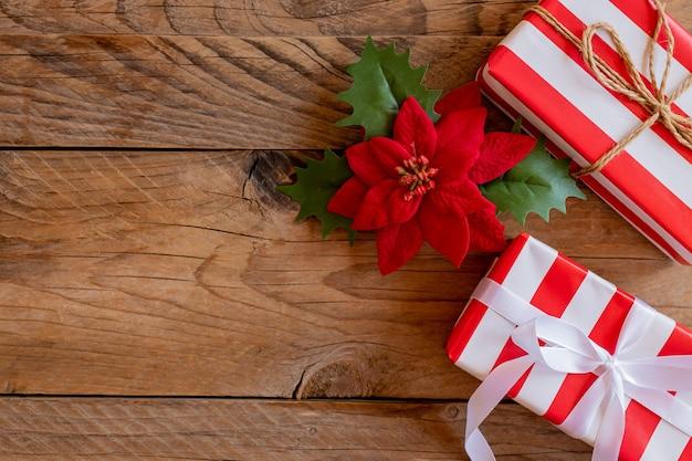 木製の背景にポインセチアとギフトのクリスマスフレーム。冬休み。あけましておめでとう。テキスト用のスペース。上から見た、フラットレイ。クリスマス。テンプレート、モックアップ。グリーティングカード。