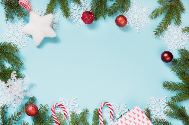Christmas frame with red balls, snowflakes and branches on blue background