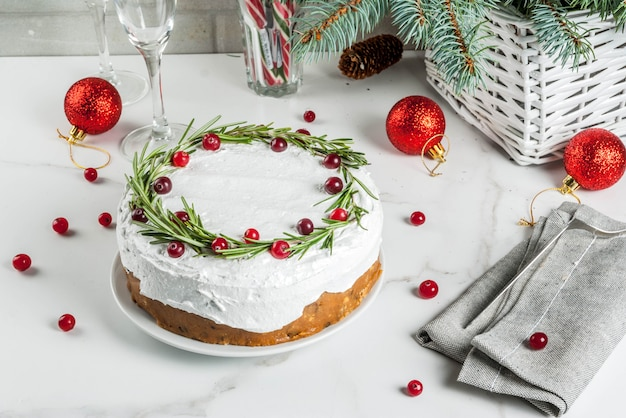 Christmas fruit cake or pudding, decorated with rosemary and cranberry, with christmas decoration, on white marble table