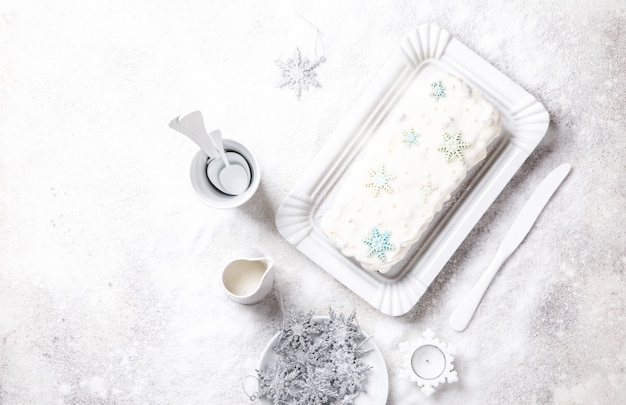 Christmas fruit cake, pudding on snowy background . new year pastries