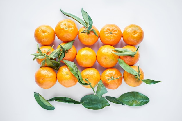 クリスマスのフルーツ。オレンジ色の新鮮なみかんや紙袋に緑の葉とマンダリンは、白い背景にあります。