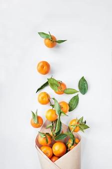 クリスマスフルーツ。オレンジ色の新鮮なみかんまたは緑の葉とマンダリンは、紙袋にあります。